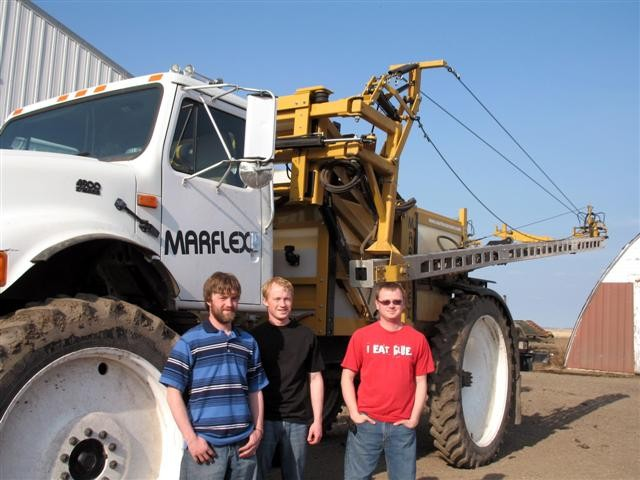 The Loll brothers Charles, Josiah, and Ben in front of their Marflex sprayer